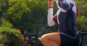 Occhiali da sole d'uso del ciclista femminile in strada 4k della campagna video d archivio