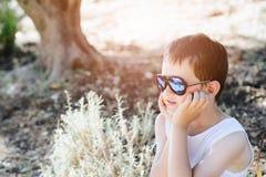 Occhiali da sole d'uso del ragazzo triste del piccolo bambino Immagine Stock Libera da Diritti