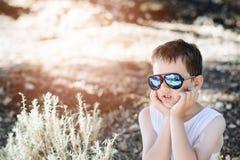 Occhiali da sole d'uso del ragazzo triste del piccolo bambino Fotografia Stock