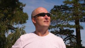 Occhiali da sole d'uso dell'uomo adulto del ritratto al giorno di estate soleggiato in foresta verde video d archivio