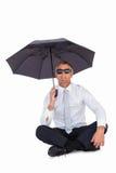 Occhiali da sole d'uso dell'uomo d'affari e riparare con l'ombrello Immagini Stock