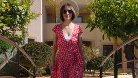 Occhiali da sole d'uso della bella donna caucasica, cappello e vestito rosso camminanti verso la macchina fotografica nel giardin stock footage