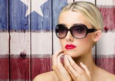 Occhiali da sole d'uso della donna abbastanza bionda contro un fondo di legno della bandiera americana Fotografie Stock Libere da Diritti