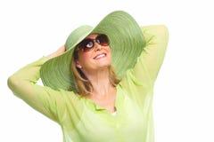 Occhiali da sole d'uso della donna e un cappello. Fotografia Stock