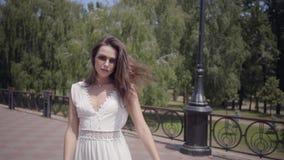 Occhiali da sole d'uso della ragazza sveglia e un vestito bianco lungo da modo di estate che cammina all'aperto Svago di una donn stock footage