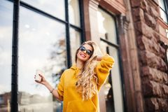 Occhiali da sole d'uso e braccialetti della ragazza graziosa che sorridono sulla via Ritratto all'aperto di risata della giovane  Immagine Stock