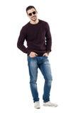 Occhiali da sole d'uso rilassati freschi e jeans del giovane che sorridono alla macchina fotografica Fotografie Stock Libere da Diritti