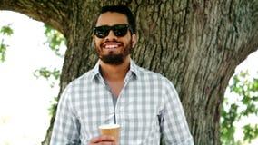 Occhiali da sole d'uso sorridenti dell'uomo che giudicano un champagne di vetro stock footage
