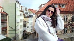 Occhiali da sole d'uso sorridenti della ragazza di modo che posano sul balcone al fondo europeo della via della città archivi video