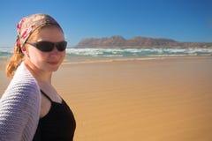 Occhiali da sole da portare della giovane donna sulla spiaggia a Muizenberg Immagine Stock
