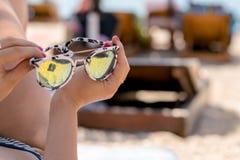 Occhiali da sole della tenuta della mano fotografia stock