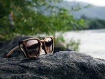 Occhiali da sole di legno al tramonto sul fiume con la riflessione fotografie stock