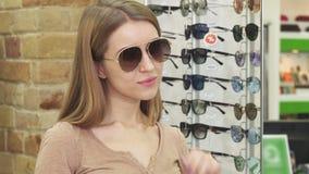 Occhiali da sole di prova della bella donna allegra al deposito dell'optometrista stock footage