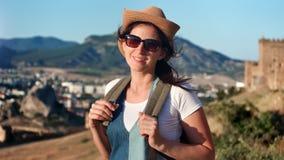 Occhiali da sole e cappello d'uso sorridenti della donna di viaggio che posano alla città circondata dal paesaggio della montagna archivi video