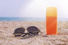 Occhiali da sole e crema del sole nella sabbia contro il mare nei raggi Immagine Stock