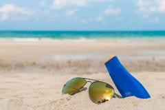 Occhiali da sole e crema del sole sulla spiaggia di sabbia bianca Fotografie Stock Libere da Diritti