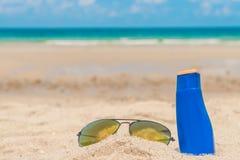 Occhiali da sole e crema del sole sulla spiaggia di sabbia bianca Fotografie Stock
