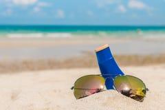 Occhiali da sole e crema del sole sulla spiaggia di sabbia bianca Immagini Stock