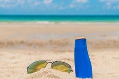 Occhiali da sole e crema del sole sulla spiaggia di sabbia bianca Fotografia Stock