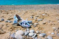 Occhiali da sole e le scarpe delle donne sulla spiaggia Immagini Stock