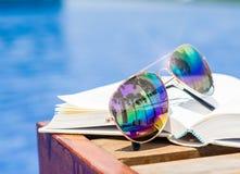 Occhiali da sole e libro del primo piano sul lato della piscina immagine stock libera da diritti