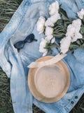 Occhiali da sole flatlay cappello di punto di vista superiore di signora di viaggio e concetto dei jeans delle peonie immagini stock