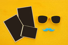 Occhiali da sole gialli dei pantaloni a vita bassa e baffi divertenti accanto alle fotografie in bianco Fotografia Stock