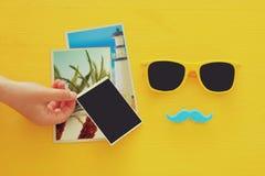 Occhiali da sole gialli dei pantaloni a vita bassa e baffi divertenti accanto alle fotografie in bianco Immagine Stock