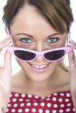 Occhiali da sole incorniciati rosa d'uso della donna felice Fotografia Stock