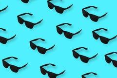 Occhiali da sole neri del modello su fondo blu pastello Concetto minimo di estate fotografie stock