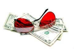 Occhiali da sole rossi che riposano sui contanti Immagini Stock Libere da Diritti