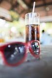 Occhiali da sole rossi con un vetro di soda ghiacciata Immagine Stock