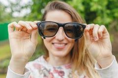 Occhiali da sole sorridenti della tenuta della ragazza in sue mani Fotografia Stock Libera da Diritti