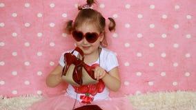 Occhiali da sole sotto forma di cuore Una signora della bambina si agghinda - borsa e scarpe rosse Bambino divertente Fondo rosa archivi video