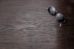 Occhiali da sole su una tavola di legno scura immagine stock