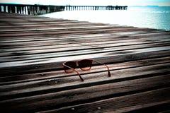Occhiali da sole sul ponte di legno Immagine Stock