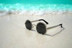 Occhiali da sole sulla spiaggia sabbiosa di estate Immagini Stock