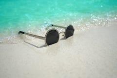 Occhiali da sole sulla spiaggia sabbiosa di estate Fotografie Stock