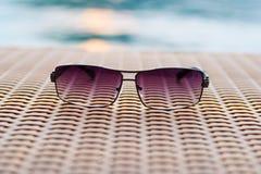 Occhiali da sole sulla tavola e sul fiume di legno (fondo d'annata) Immagini Stock