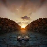Occhiali da sole sulle rocce a bella alba di tramonto Fotografia Stock
