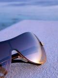 Occhiali da sole tinti bronzo che riflettono tramonto Immagine Stock
