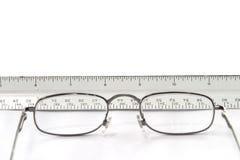 Occhiali della lettura sulla tabella con la vista del righello attraverso i vetri Fotografia Stock