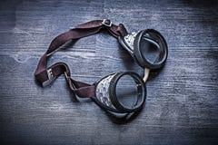 Occhiali di protezione d'annata sul bordo di legno Fotografie Stock