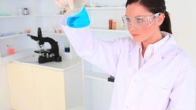 Occhiali di protezione d'uso del giovane scienziato ed esaminare una boccetta archivi video