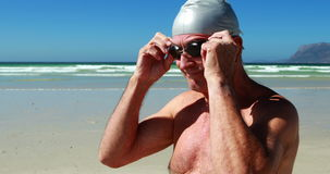 Occhiali di protezione d'uso di nuotata dell'uomo senior alla spiaggia archivi video