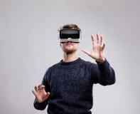 Occhiali di protezione d'uso di realtà virtuale dell'uomo Colpo dello studio, backgroun grigio Fotografie Stock Libere da Diritti