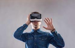 Occhiali di protezione d'uso di realtà virtuale dell'uomo Colpo dello studio, backgroun grigio Fotografia Stock