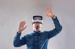 Occhiali di protezione d'uso di realtà virtuale dell'uomo Colpo dello studio, backgroun grigio Immagini Stock Libere da Diritti