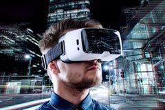 Occhiali di protezione d'uso di realtà virtuale dell'uomo contro la città di notte Fotografie Stock