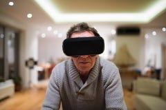 Occhiali di protezione d'uso di realtà virtuale dell'uomo senior a casa Fotografie Stock Libere da Diritti